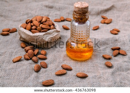 Bottle of extra virgin almonds oil with whole almonds on hempsack background. - stock photo