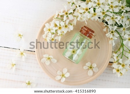 Bottle of flower aroma water, orchard spring blossom twigs. Herbal cosmetics.