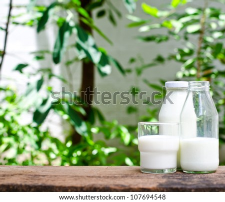 Bottle of fresh milk and glass on a wooden table - stock photo