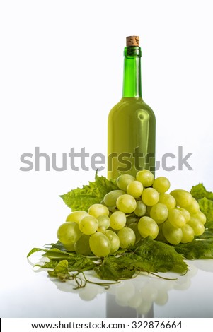Bottle of fresh white wine with green grapes on white background