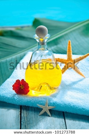Bottle of golden essential oil plant extract on a towel alongside a pool ready for an aromatherapy spa treatment - stock photo