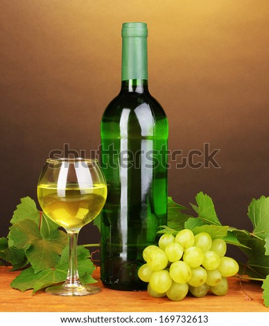 Bottle of great wine with glass on wooden table on brown background