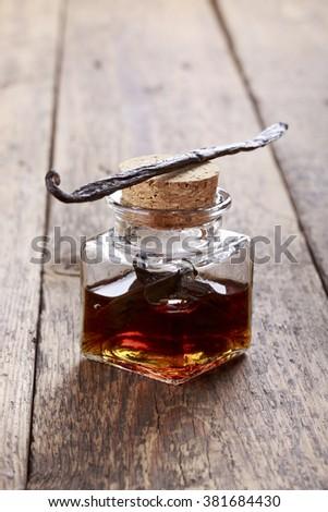 Bottle of homemade vanilla essence on wooden background - stock photo