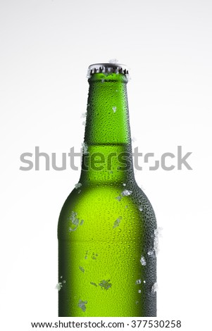 Bottle of ice cold beer with ice and drops