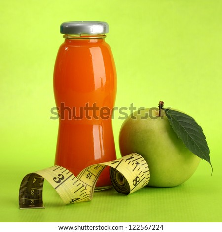 bottle of juice, apple and measuring tape, on green background - stock photo