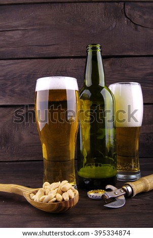 Bottle of lager beer and glass goblets on a wooden background. Friendly meeting. - stock photo