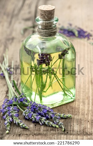 bottle of lavender oil with fresh flowers on wooden background. healthy herbs. selective focus - stock photo