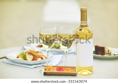 Bottle of luxury wine with tasty salad on white served table - stock photo