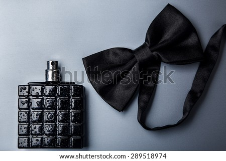 Bottle of male perfume and black bow tie  - stock photo