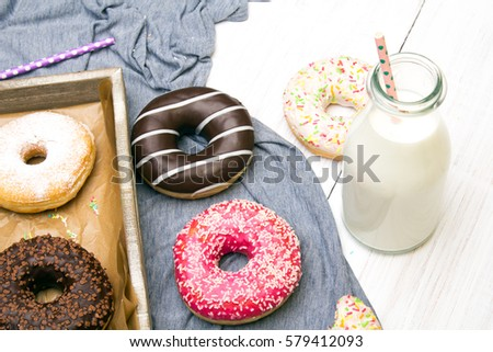 Bottle of milk and colorful donuts with chocolate and icing, selective focus