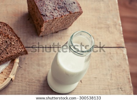 Bottle of milk and slices of rye brown bread on rustic wooden table