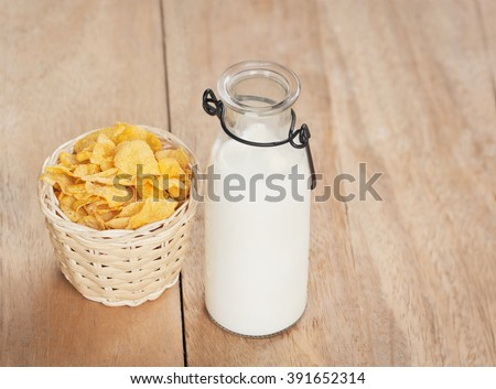 bottle of milk with Corn Cereals on wooden table. - stock photo
