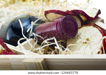 Bottle of old red wine in gift wooden box with apple - stock photo