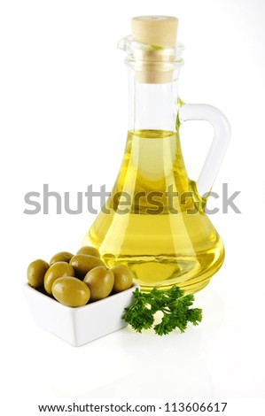 bottle of olive oil isolated on white with olives on small plate