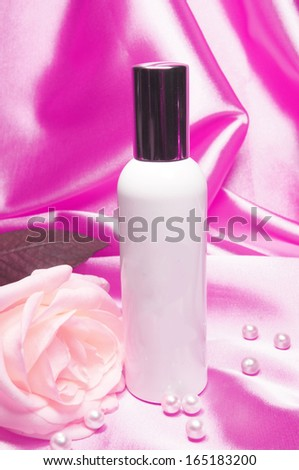 Bottle of perfume and rose with pearls on pink satin  - stock photo
