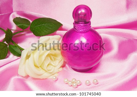 bottle of perfume and white rose - stock photo