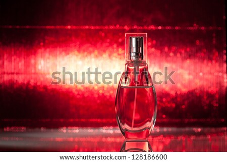 Bottle of perfume on shiny red background