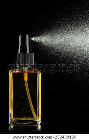 bottle of perfume spraying on black background - stock photo