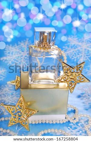 bottle of perfume standing on golden box in christmas scenery - stock photo