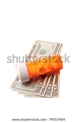 bottle of pills laying on money - stock photo
