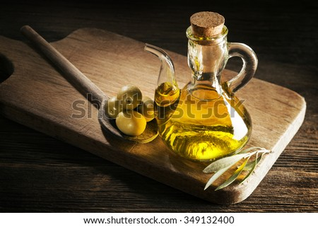 Bottle of premium virgin olive oil and some olives with leaves. - stock photo