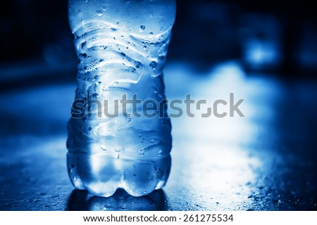 Bottle of  pure water with condensate drops and back light - stock photo
