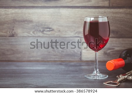 Bottle of red wine and glass on wooden table with corkscrew - stock photo