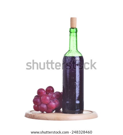 Bottle of red wine and grapes on wooden plate isolated on white - stock photo