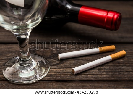 Bottle of red wine and two cigarettes with empty wineglass on an old wooden table. Close up view, focus on the cigarette - stock photo