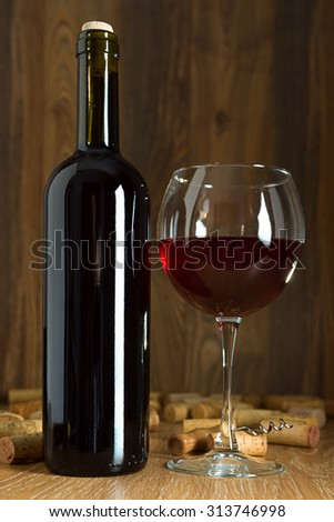 Bottle of red wine and wine glass, cork and corkscrew - stock photo