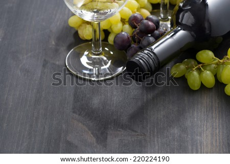 bottle of red wine, empty glass and grapes on a dark wooden background, horizontal - stock photo