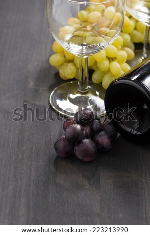 bottle of red wine, empty glass and grapes on a wooden background, vertical - stock photo