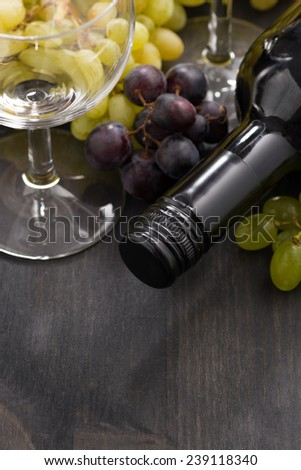 bottle of red wine, empty glass and grapes on a wooden background, vertical, close-up - stock photo