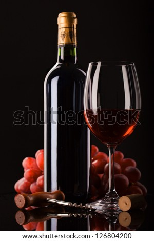 bottle of red wine, glass and grapes on dark background with place for text - stock photo