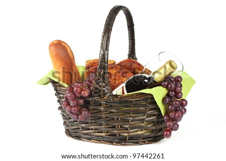 bottle of red wine glass grapes bread and chicken in picnic basket on white background - stock photo