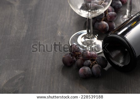 bottle of red wine, glasses and grapes on a wooden background, horizontal - stock photo