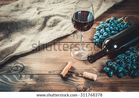Bottle of red wine, grape and corks on wooden table
