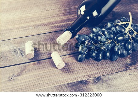 Bottle of red wine, grape and corks on wooden table - stock photo
