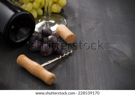 bottle of red wine, grape and corkscrew on a wooden background, horizontal - stock photo