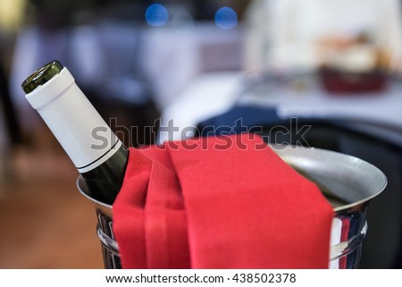 bottle of Red Wine in Ice bucket with red cloth - stock photo