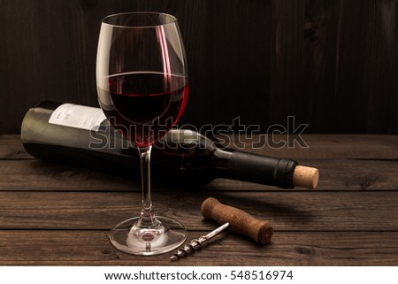 Bottle Of Red Wine With A Glass And Corkscrew On An Old Wooden Table. Focus
