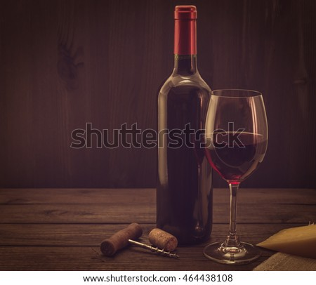 Bottle of red wine with a glass and corkscrew with a piece of parmesan on an old wooden table. Image vignetting and the yellow toning