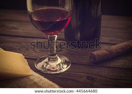 Bottle of red wine with a glass of red wine and a piece of parmesan and cuban cigar on an old wooden table. Angle view, focus on the glass of red wine, image vignetting and the yellow toning