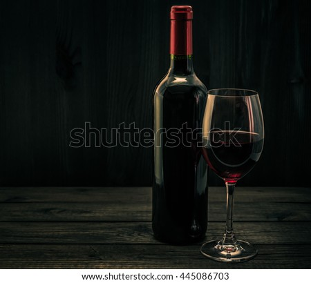 Bottle of red wine with a glass of red wine on an old wooden table. Image vignetting and the orange-blue toning