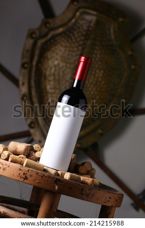 Bottle of red wine with blank label template standing on an old wooden stool with used corks and an iron shield and weaponry in the background
