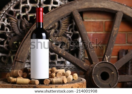 Bottle of red wine with blank label template standing on an old wooden stool with used corks near the fireplace - stock photo