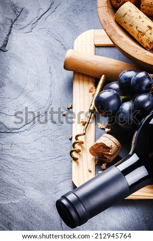 Bottle of red wine with fresh grape and corkscrew - stock photo