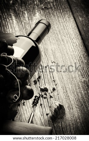 Bottle of red wine with fresh grape and corkscrew. Black and white concept  - stock photo