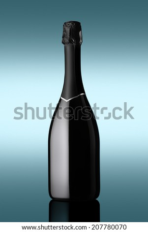 bottle of sparkling wine on blue background with light effects - stock photo