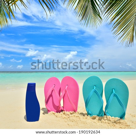 Bottle of sunscreen lotion and colored flip-flops on the tropical beach -- Summer holidays concept - stock photo